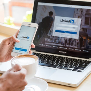 A phone held up in front of a laptop, both with a picture of the Linkedin sign on page